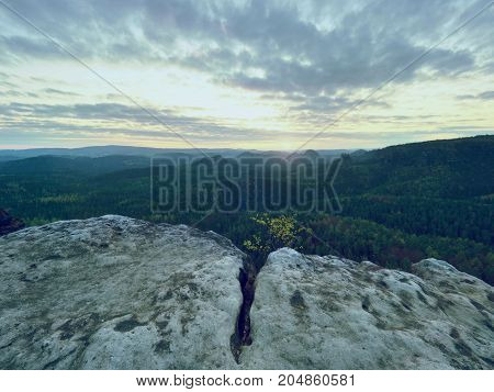 Spring Morning Nature. The Cracked Sandstone Cliff Above Forest Valley, Daybreak Sun At Horizon