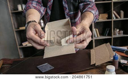 Manual assembly. Young man leather maker manually assemble cardboard packaging box for various leather products in handmade style. Creative business in home workshop