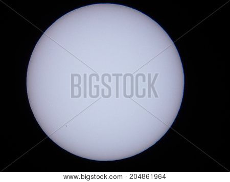 the sun viewed through a solar filter in a telescope with sunspot visible