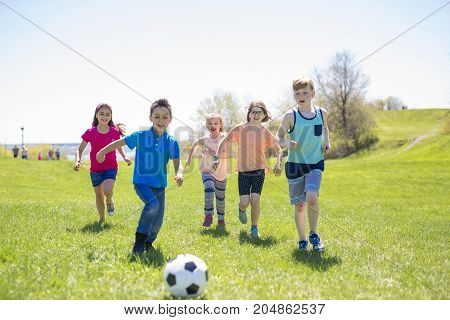 Boys and girls running towards ball on a field