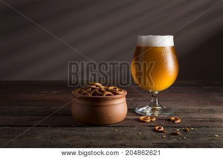 Glass of cold pale beer with a bowl of pretzels on a rustic wooden table