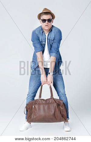 Handsome young man in denim raises heavy leather bag on grey background