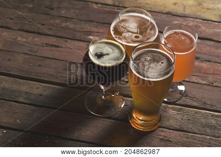 Pale dark unfiltered pale and red fruit beer in four different beer glasses on a rustic wooden table. Selective focus