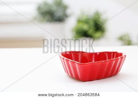 Red heart shaped dish on a white table