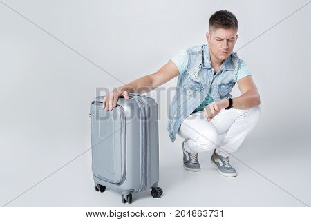 upset young man in denim vest with suitcase looking at watch against grey background