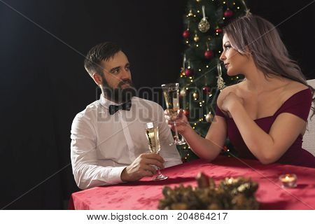 Young attractive couple enjoying romantic Christmas dinner drinking champagne and making a toast. Focus on the guy