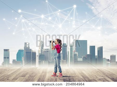 Cute girl is standing on a wooden floor and watching through binoculars