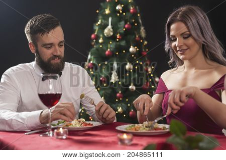 Attractive young couple enjoying a romantic Christmas dinner. Focus on the guy