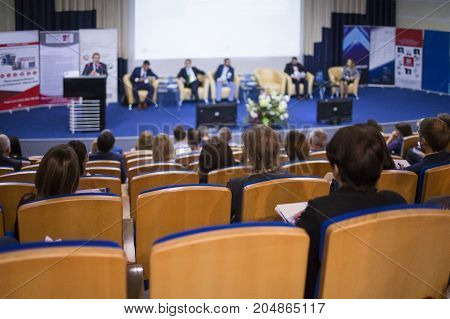 Business Concepts. Male Host Speaking On Stage During Business Conference in Large Congress Hall. Ideas Entrepreneurship. Horizontal image Composition