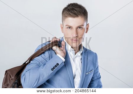 portrait of Handsome fashion young man in blue suit carrying leather bag on shoulder and looking at camera against grey background
