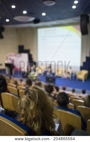 Business and Entrepreneurship Ideas. Female Speaker On Stage Giving a Talk at Business Meeting or Conference. Back View of the Listeners.Vertical Image Orientation