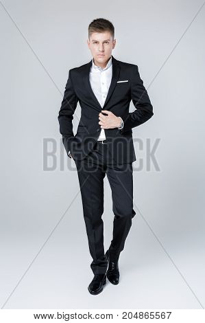 elegant successful man in suit. Business man standing and looking at the camera