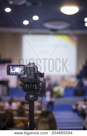 Back View of Professional Videocamera. Positioned Against Blurred Background. Vertical Image