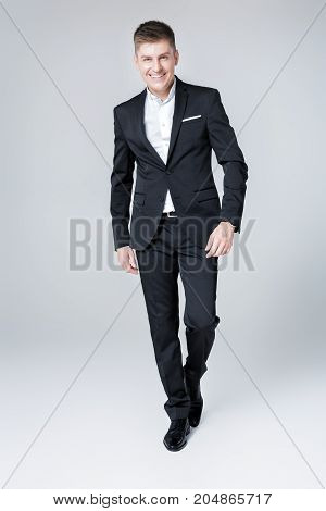 elegant successful smiling man in suit. Business man standing and looking at the camera