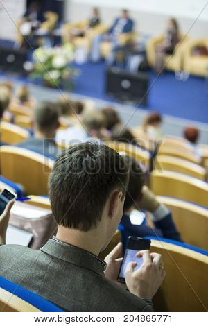 Business Conferences Concept and Ideas. Back of Male Congress Participant Listening to The Lecturer Speaking In front of the Group of People. Vertical Image Composition