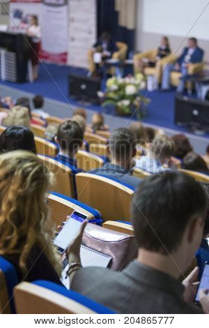 Business Conferences Concept and Ideas. Back of Congress Participants Listening to The Lecturer Speaking In front of the Group of People. Vertical Image Orientation