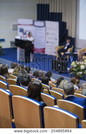 Business Conferences Concepts and Ideas. Group of People Attending Conference and Listening to the Host Speaker. Back View.Vertical Image Orientation