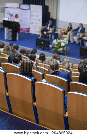 Business Concepts. Group of Hosts Sitting on Stage At Table During a Conference. Female Lecturer Giving a Talk on Stage in Front of the Audience. Vertical Image
