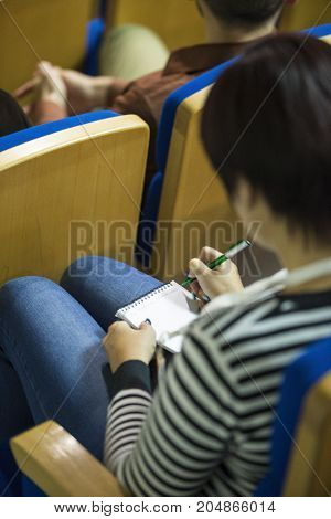 Blurred Image of Female At The Conference Making Notes in Notebook. Vertical Image