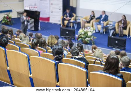 Business Ideas and Concepts. Male Host Speaking in Front of The Stage To The Audience During Business Conference in Large Congress Hall. Ideas Entrepreneurship. Horizontal image