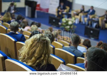 Business Concepts. Male Host Speaking in Front of The Stage To The Audience During Business Conference in Large Congress Hall. Ideas Entrepreneurship. Horizontal image Composition