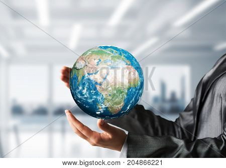 Cropped image of business woman in suit holding Earth globe in hands with office view on background. Elements of this image are furnished by NASA.
