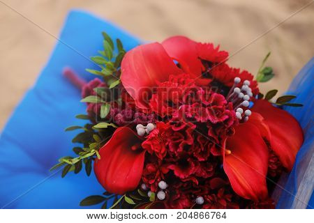 Wedding decoration. Bridal bouquet made of beautiful red flowers placed at the chair with blue cushion.