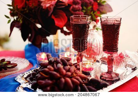 Dinner for two. Romantic table setting for a couple of lovers with glasses of red wine grapes candies and candlelight.