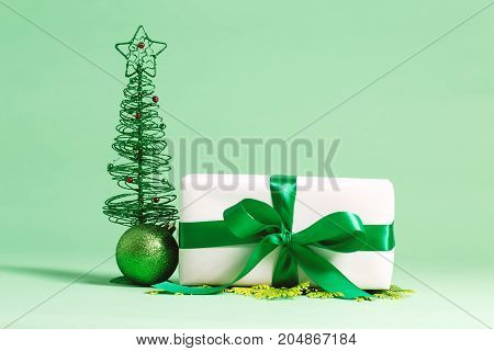 Present box with bauble Christmas ornaments on a green background