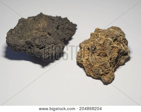 close up ochre and beige gray natural lava stones on white background