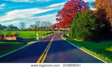 Colorful trees with blues skies along winding country road in Warrenton Missouri