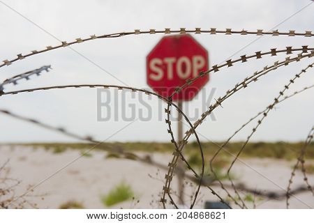 Red stop sign on beach behind safety fence of barbed wire. Focus on barbed wire.