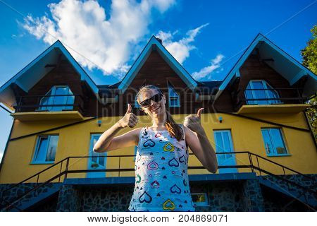 Happy young businesswoman in sunglasses bought a big home for his family. Woman standing with thumbs up standing near her new home