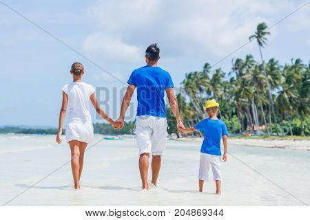 Back view of family of three - father with his child having fun at the white tropical beach