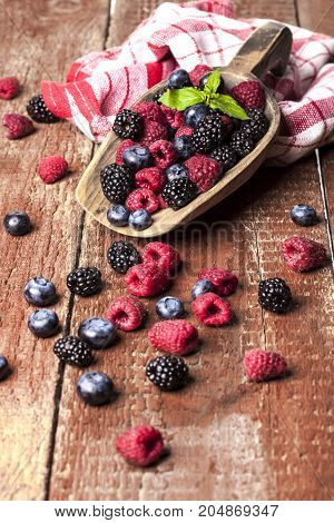 Ripe and sweet berries in spoon on wooden table