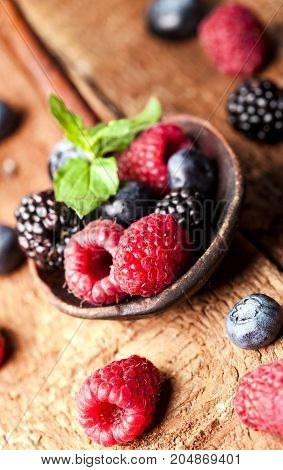 Ripe and sweet berries on spoon on wooden table