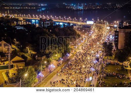 Aerial view to Stepan Razin Street in Voronezh, Russia. Crowd of people are walking along streets to look at firework at festival