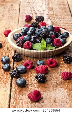 Ripe and sweet berries in bowl on wooden table