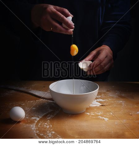 older women hands breaking an egg with falling egg yolk over a bowl wooden kitchen board dark background with copy space selected focus