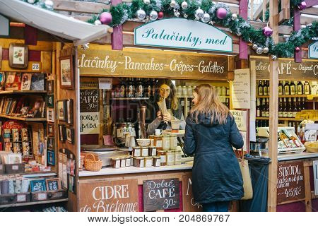 Prague, December 15, 2016: The seller offers the buyer a wide selection of honey and various wines. Christmas Market. The buyer is happy with the purchase. Celebrating Christmas.