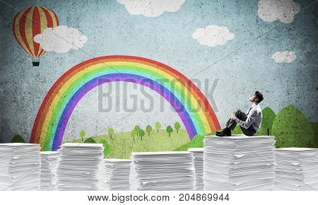 Thoughtful businessman looking away while sitting on pile of documents with drawn landscape on background. Mixed media.