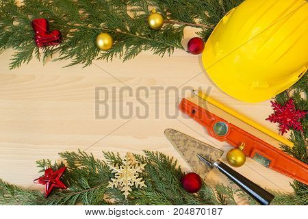 Protective Helmet, Mason Tools  And Christmas Decorations On Wooden Background
