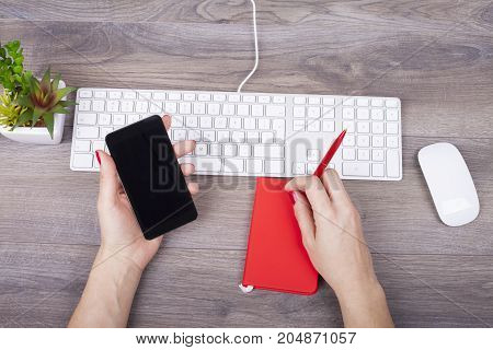 Female Hand Writing In A Notebook And Use A Mobile Phone On The Desk With A Keyboard