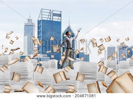 Man in casual wear keeping hand with book up while standing among flying books with cityscape on background. Mixed media.