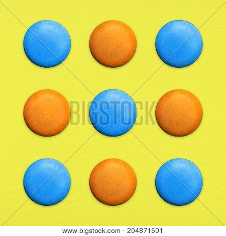 Macaroons Top view Nine orange and blue sweet macaroons or macaron on yellow background French dessert Trendy bright photo in pop art style