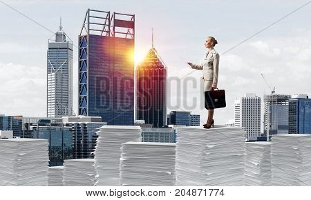 Confident business woman in suit standing on pile of documents with cityscape and sunlight on background. Mixed media.