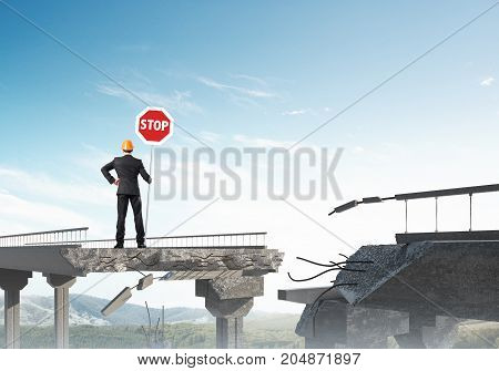 Rear view of engineer in helmet holding stop sign while standing on broken bridge with skyscape and nature view on background. 3D rendering.