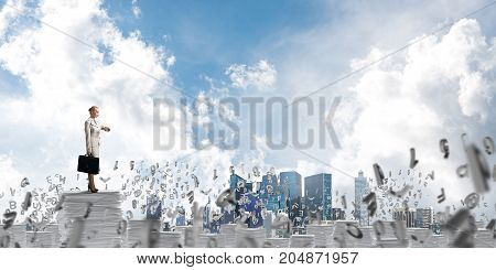 Confident business woman in suit standing among flying letters with cloudly skyscape on background. Mixed media.