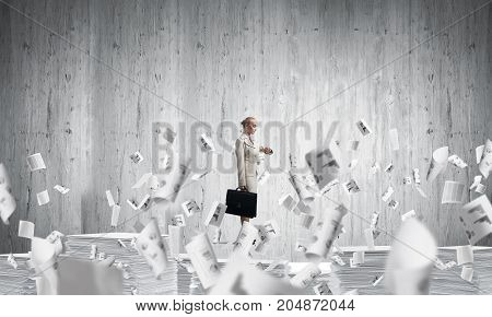 Confident business woman in suit standing among flying paper documents with grey wall on background. Mixed media.