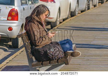 PUNTA DEL ESTE, URUGUAY, AUGUST - 2016 - Young woman listening music at boardwalk in Punta del Este city Uruguay